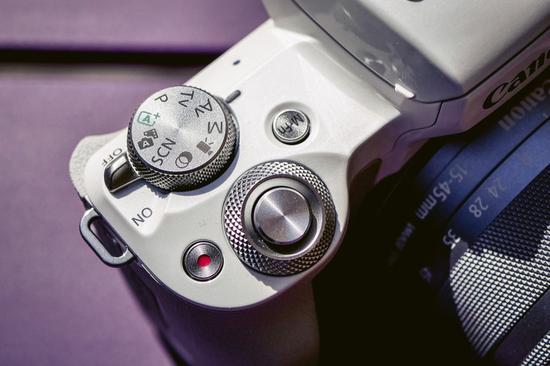 相比于EOS M5的双转盘设计,EOS M50机顶只有一个拍摄模式转盘