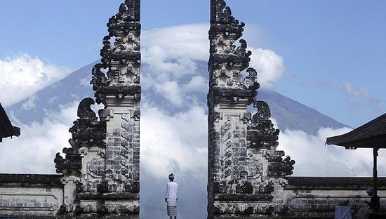 当地时间2017年9月26日,印尼巴厘岛,一名男子在寺庙中看着阿贡火山。来源:东方IC