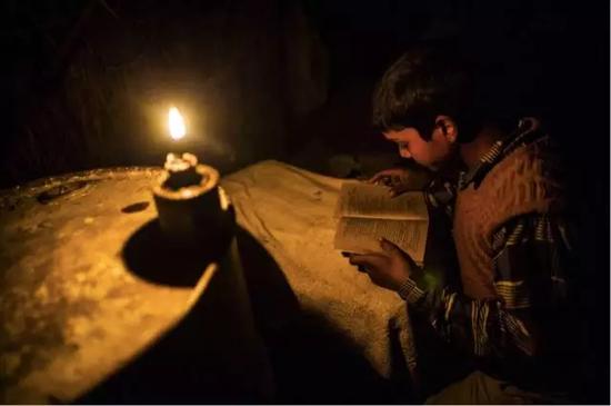 ▲Fateh Nagla村里,一名男孩在煤油灯的照明下学习(图片来源:彭博社)