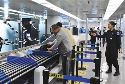 旅客在安检通道,使用人脸识别系统交运行李过安检。通讯员 王文正 摄