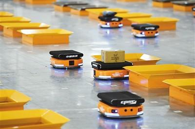 如今,智能机器人在快递分拣领域的应用大幅提升了快递效率。图为中国邮政速递物流华中(武汉)陆运中心启用机器人分拣邮件。