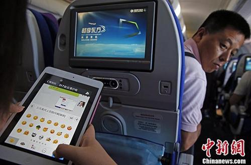 资料图为旅客在东航实际承运的航班上使用平板电脑(Pad),进行空地互联微信聊天。 中新社记者 殷立勤 摄