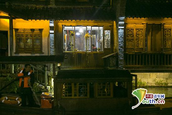 傍晚,乌镇景区内,前来参观的客人在店内用餐,窗外河面上一艘蓬船划过。中国青年网记者 宋继祥 摄
