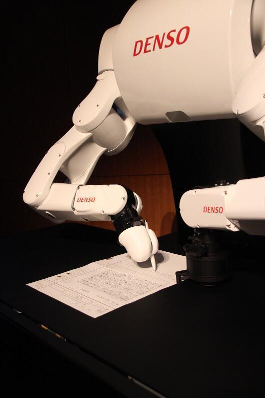 """2016年11月14日,人工智能系统""""Torobo-kun""""在东京的千代田区参加一次模拟大学入学考试,正用机械臂填写答案"""