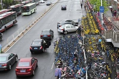 今年4月19日,昌平区龙泽地铁站,很多共享单车堆放在机动车道上,导致三车道变成两车道。 新京报记者 王飞 摄
