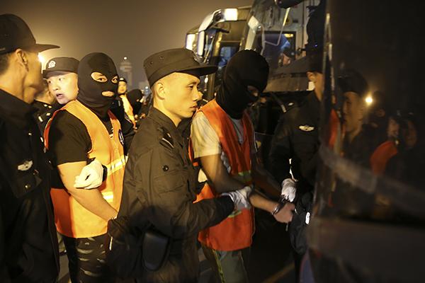 民警将犯罪嫌疑人押解至押运车辆