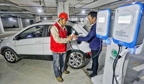 资料图片:10月27日,国网北京电力公司的技术人员在为新能源汽车进行试验充电。新华社记者 李欣 摄