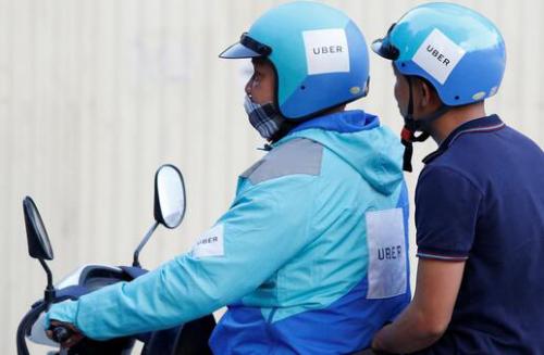 一名Uber司机在越南河内骑着一辆摩托车搭载乘客(来自路透社)