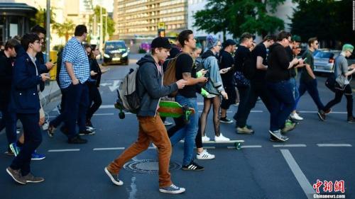 资料图:行人过马路时刷手机。