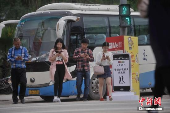 """资料图:重庆一红绿灯处摆放了""""不做低头族、关注红绿灯""""警示牌。 陈超 摄"""