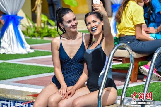 资料图:两名女子在泳池边自拍。骆云飞 摄