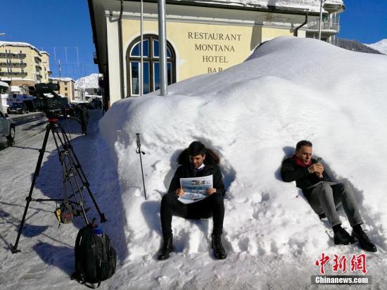 """资料图:当地时间2018年1月23日,2018年世界经济论坛年会(""""冬季达沃斯"""")在瑞士小城达沃斯开幕。今年的冬季达沃斯年会开幕前夕,当地迎来了多年不遇的强降雪。图为两名记者当天坐在积雪上休息。中新社记者 彭大伟 摄"""